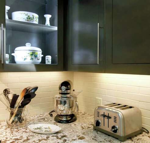 LED lights illuminate glass-fronted upper cabinets. With a microwave, toaster oven, electric skillet and coffeepot set up in the office, the Bakers still ate most meals at home during the three-month renovation. Photo: WILLIAM LUTHER, SAN ANTONIO EXPRESS-NEWS / 2011 SAN ANTONIO EXPRESS-NEWS