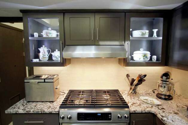Bianco Antico granite, a crisp pattern of white and chocolate, replaces the turquoise laminate counters. White subway tiles on the backsplash satisfy Dolly's quest for a clean look she won't tire of. Photo: WILLIAM LUTHER, SAN ANTONIO EXPRESS-NEWS / 2011 SAN ANTONIO EXPRESS-NEWS