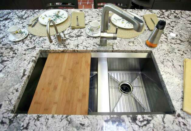 "A cutting board that fits into the stainless sink is a first for Dolly. ""I never had a cutting board before that was handy."" Photo: WILLIAM LUTHER, SAN ANTONIO EXPRESS-NEWS / 2011 SAN ANTONIO EXPRESS-NEWS"