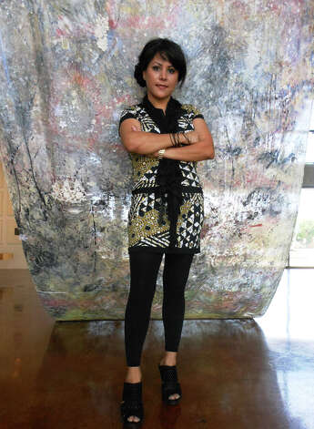 "Carla Veliz stands with ""XXI,"" a piece of silk that took 21 days of abuse, then 21 days of repair. STEVE BENNETT / EXPRESS-NEWS"