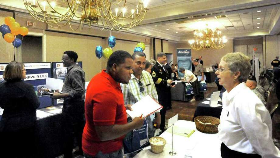 Francisco Madina, left center, and Welington Sencion, center, both of Danbury, talk with Karen Keck of the American Red Cross during the Danbury Jobs Fair at Ethan Allen Inn Monday, Sept. 12, 2011. Photo: Michael Duffy