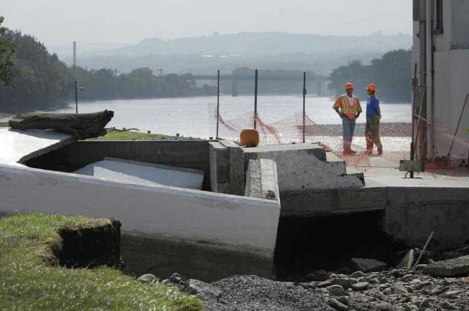 Workers look over some of the destruction at Lock 11 on the Erie Canal in Amsterdam on Monday, Sept. 12, 2011.  The flooding of the Mohawk River severely damaged the flood gates by the lock and  many of the buildings.  (Paul Buckowski / Times Union) Photo: Paul Buckowski  / 00014589A