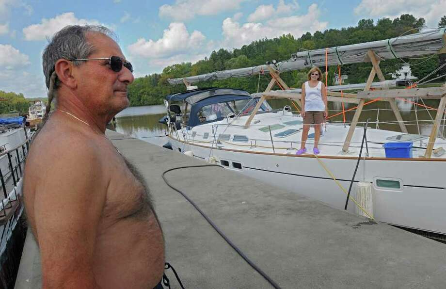 Dick Dragonette of Cleveland, Ohio talks about  the trip down the Erie Canal in his sail boat docked at Lock 3 in Waterford, N.Y. Monday, Sept. 12, 2011. His wife Margaret stands on their boat to the right. (Lori Van Buren / Times Union) Photo: Lori Van Buren