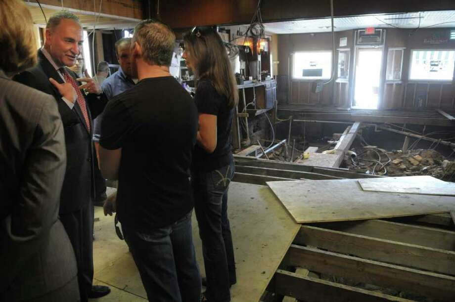 Senator Charles Schumer, left, talks with Russo's Grill owner Mike Russo and his wife Barbara Russo as they stand inside the restaurant on West Main St. in Amsterdam on Monday, Sept. 12, 2011.  The recent flooding of the Mohawk River destroyed the floor of the business.  The restaurant is located across the street from Lock 11 on the Erie Canal.  The lock also suffered major damage from the flood.   Senator Schumer along with Congressman Paul Tonko, Amsterdam Mayor Ann Thane and Brian Stratton, director of the State's Canal Corporation took a tour of the lock on Monday. (Paul Buckowski / Times Union) Photo: Paul Buckowski  / 00014589A