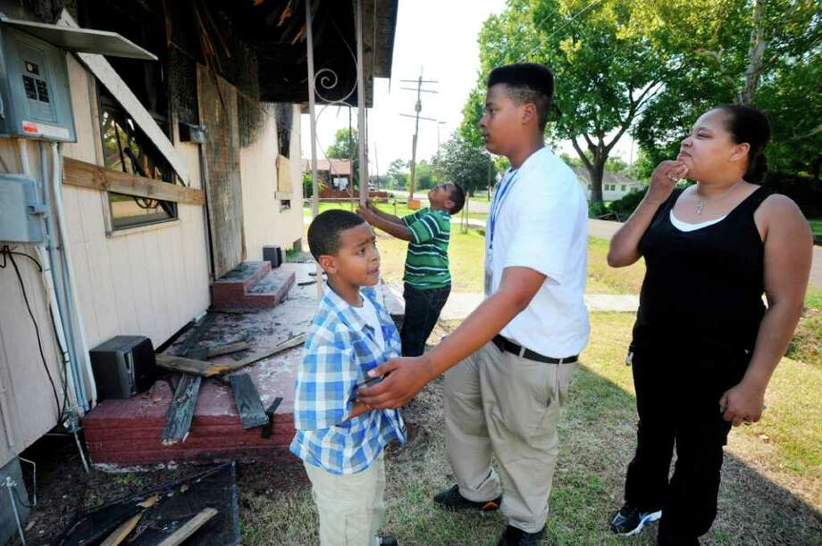 Darcus Broussard, right, and her children, Jonathan, 8 (left), Alexander, 6 (center), and Thomas, 14, examine the remains of their south Beaumont home, which was lost to a fire Sept. 2. Broussard and her children escaped before the fire gutted the home. Photo: Valentino Mauricio
