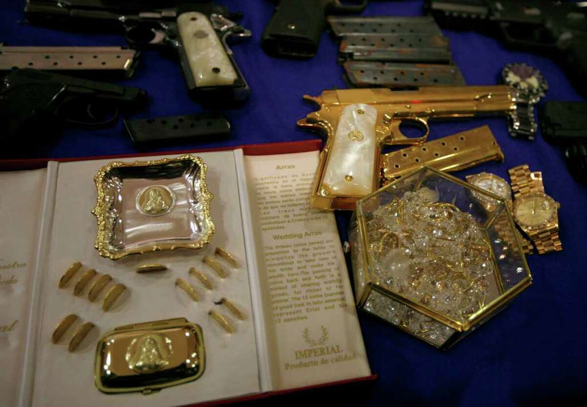 """A gold plated pistol and jewelry, allegedly seized from Manuel Alquisires Garcia, alias """"El Meme,"""" sit on display during his presentation to the press of in Mexico City, Monday Sept. 12, 2011."""
