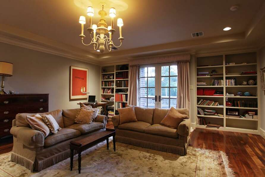 Another well-lit living area filled with multiple built-in bookshelves.