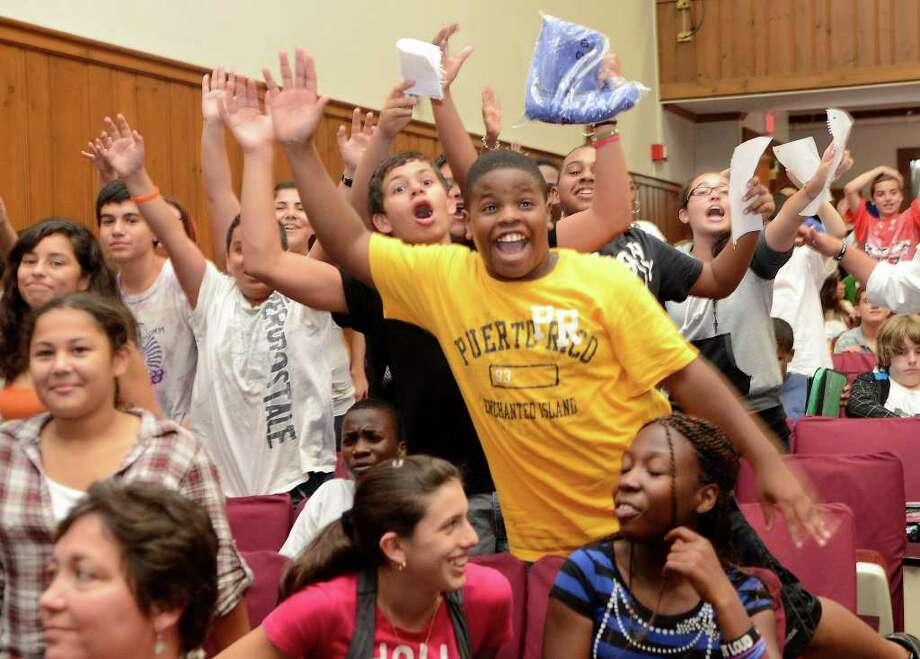 Dolan Middle School students Greg Lapeine, 13 (yellow shirt) and Trevor Kaufman, 13 (black shirt), raise their hands to answer a trivia question posed by a member of the New York Giants in Stamford CT on Tuesday, September 13, 2011. Photo: Shelley Cryan / Shelley Cryan freelance; Stamford Advocate freelance