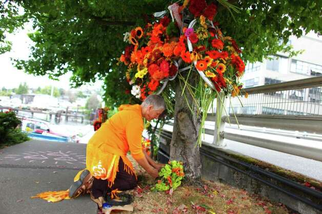 Sue Scharff places flowers at a 'ghost bike' memorial after bicycle commuter and local barista Brian Fairbrother crashed his bicycle in late August. He recently died from the accident. Fairbrother died when his bike went down stairs on Fairview Avenue East. The stairs are difficult to see while traveling on the bike path. Photographed on Tuesday, September 13, 2011. Photo: JOSHUA TRUJILLO / SEATTLEPI.COM