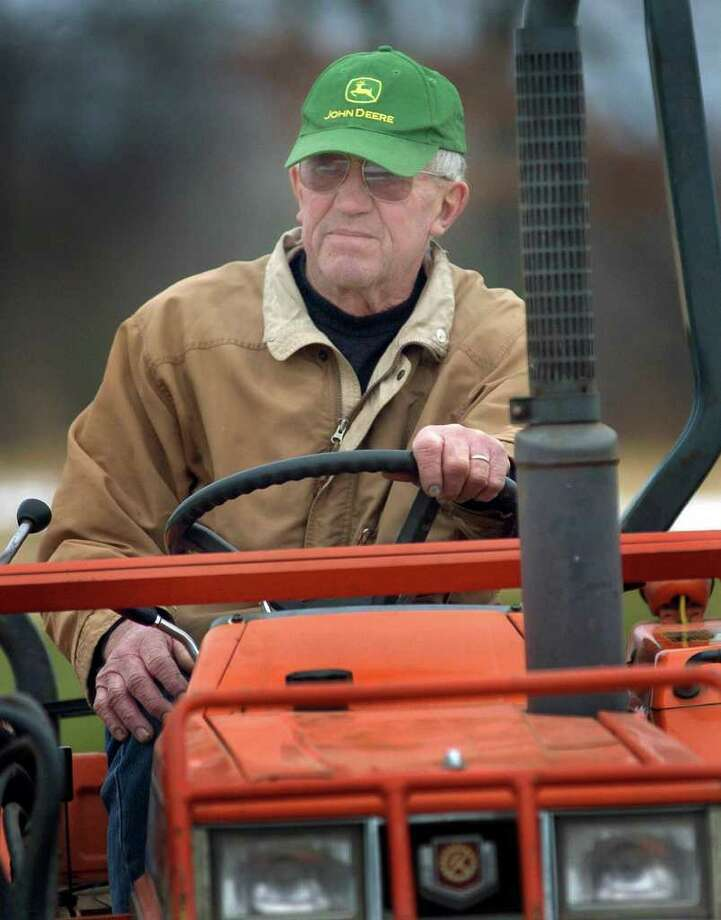George Harris looks over his land from his tractor on his Harris Hill Farm in New Milford in this Dec. 2007 file photo. Photo: Carol Kaliff