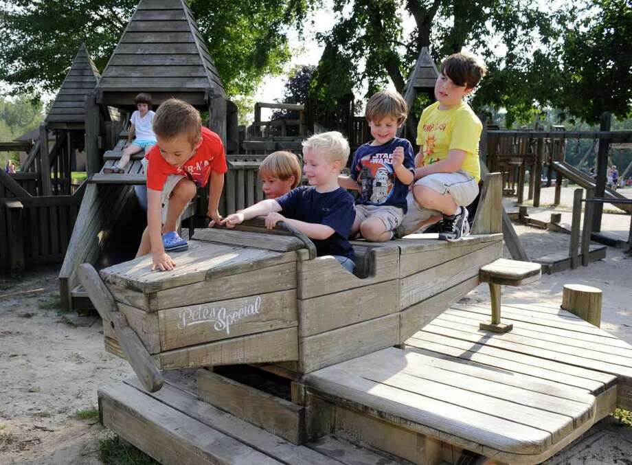 Kids play on the airplane at the Kids' Kingdom playground in Brookfield Tuesday. From left in foreground, Gordon Bennett, 5, of Newtown, Carson Bennett, 3, Mason Schell, 5, of New Milford, Eddie Lundquist, 4, of Newtown and his brother Matt, 10. Photo taken Tuesday, Sept. 13, 2011. Photo: Carol Kaliff / The News-Times
