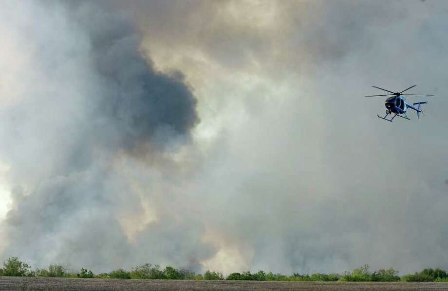 CODY DUTY : CHRONICLE GRAY BARRICADE: A helicopter prepares to land Tuesday as a wall of smoke rises from a fire in George Bush Park, Photo: Cody Duty / © 2011 Houston Chronicle