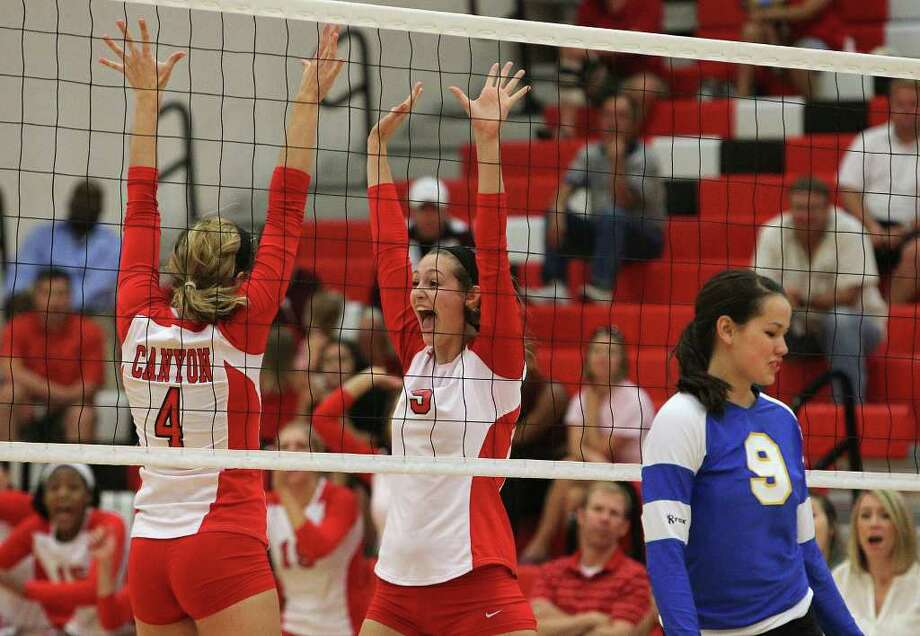 New Braunfels Canyon's Rafae Strobos (05) reacts with teammate Jenna Taylor (04) after scoring against Alamo Heights' Jemma Miller (09) in New Braunfels on Tuesday, Sept. 13, 2011. The Cougarettes defeated the Mules in three straight games to take the victory. Photo: Kin Man Hui/kmhui@express-news.net / SAN ANTONIO EXPRESS-NEWS