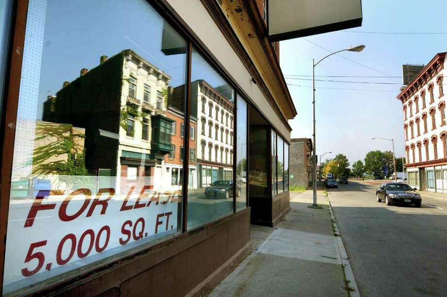 Buildings reflect in the storefront window of 32 King St. on Tuesday, Sept. 13, 2011, in Troy, N.Y. The building is a proposed site of a new restaurant or bar. (Cindy Schultz / Times Union) Photo: Cindy Schultz