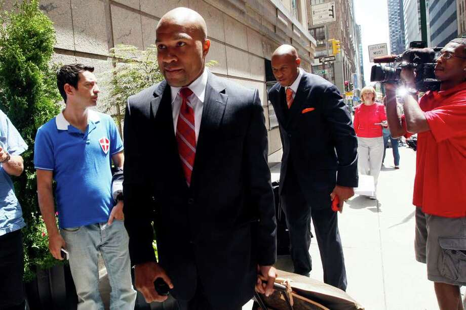 National Basketball Players Association union president Derek Fisher, center, of the Los Angles Lakers, and Maurice Evans, center right, of the Washington Wizards, arrive at a midtown hotel for a meeting Thursday, June 30, 2011 in New York. Negotiators for owners and players are meeting Thursday, about 12 hours before the expiration of the collective bargaining agreement and seemingly nowhere close to a deal. (AP Photo/Mary Altaffer) Photo: Mary Altaffer