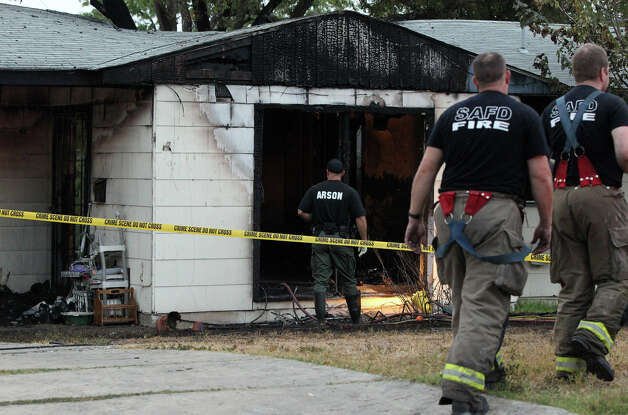 An arson investigator enters a home early Wednesday morning, Sept. 14, 2011 in the 200 block of Karen Lane, where a fire broke out at about 3:30 a.m. According to SAFD Captain Fernando Sosa, two people were found dead in the home. One was a woman in her 40s and the other is believed to be an 11-year-old girl. Another body was found later in the day. Photo: John Davenport/jdavenport@express-news.net