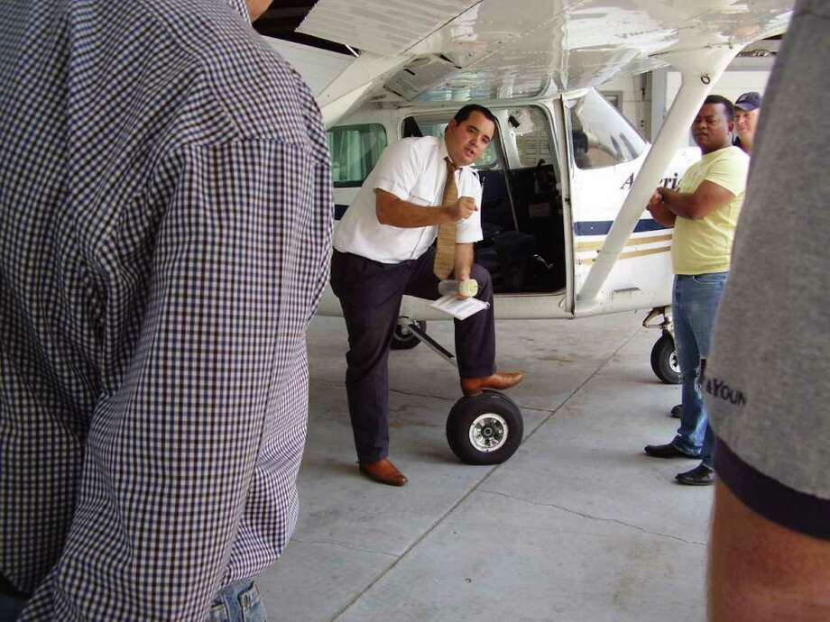 Flight Instructor Darial Pedron does a pre-flight inspection with potential flight students at American Fliyers Academy at Hooks Municipal Airport. American Flyers has about 25 flight students enrolled in various programs.  03: A potential flight student enjoys a cheese burger while checking out a Cessna 172RG single engine aircraft at the American Flyers Academy at Hooks Municipal Airport. Photo: Bryan Kirk