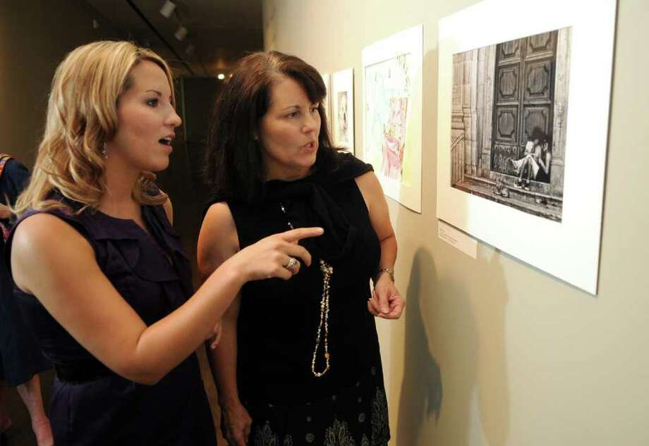 """JERRY BAKER: For the Chronicle SETTING THE TONE: Sarah Kelly, left, an art teacher at Mueller Elementary, talks about her digital photograph """"La Nostra Familia"""" with her mother, Melinda Jahn, an art teacher and department head at Stack Intermediate, during an artists' reception and exhibition at the Pearl Fincher Museum of Fine Arts in Spring. Photo: Jerry Baker"""