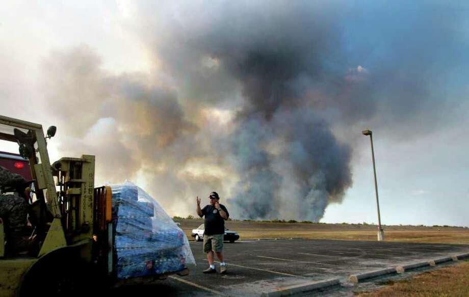El bombero de Katy Kevin Caufman (der.) envía a su compañero Marcus Taylor a una zona de descanso mientras ambos tratan de apagar la llamas en el incendio forestal en el George Bush Park, al oeste de Houston. Photo: Cody Duty / © 2011 Houston Chronicle