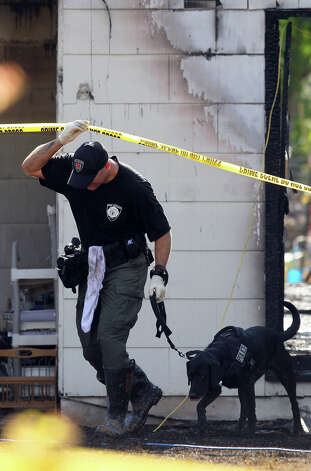 An arson investigator and his dog exit a home in the 200 block of Karen Lane, where a fire broke out at about 3:30 a.m. Wednesday, Sept. 14, 2011. According to SAFD Captain Fernando Sosa, two people were found dead in the home. One was an adult woman and the other is believed to be an 11-year-old girl. A third body was found later in the day. Photo: John Davenport/jdavenport@express-news.net