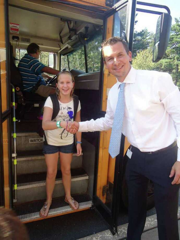 Royle School Principal Keith Margolus greets fifth-grader Hannah Felske as she steps off the bus on the first day of school. Photo: Contributed Photo