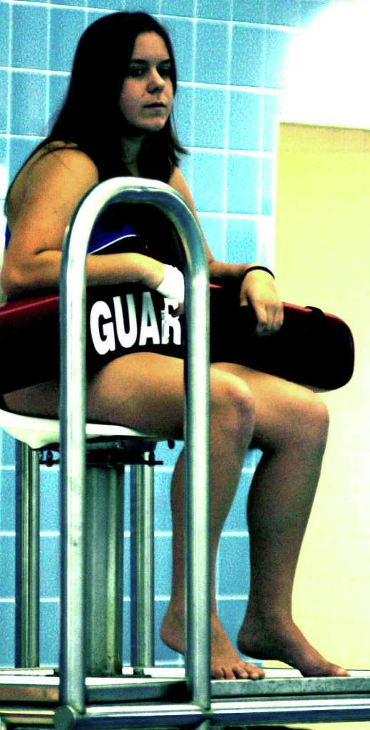 SPECTRUM/Brice Schrenkel of New Milford High School girls' swimming keeps busy as lifeguard for a practice while she awaits her return from injury, September 2011