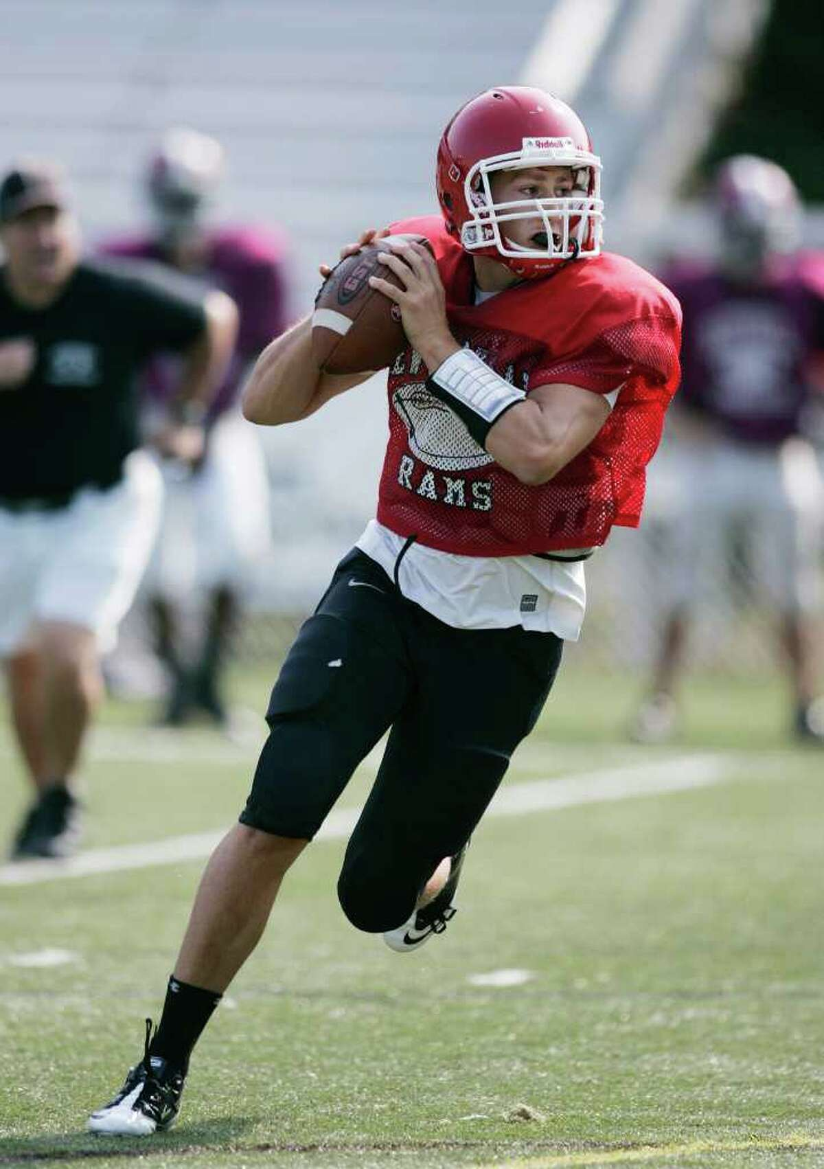 Senior New Canaan High School QB Matt Milano rolls right and looks for a open receiver during a controlled scrimmage session against Stepinac HS. Milano is expected to figure big again in the Rams offensive plans this season.