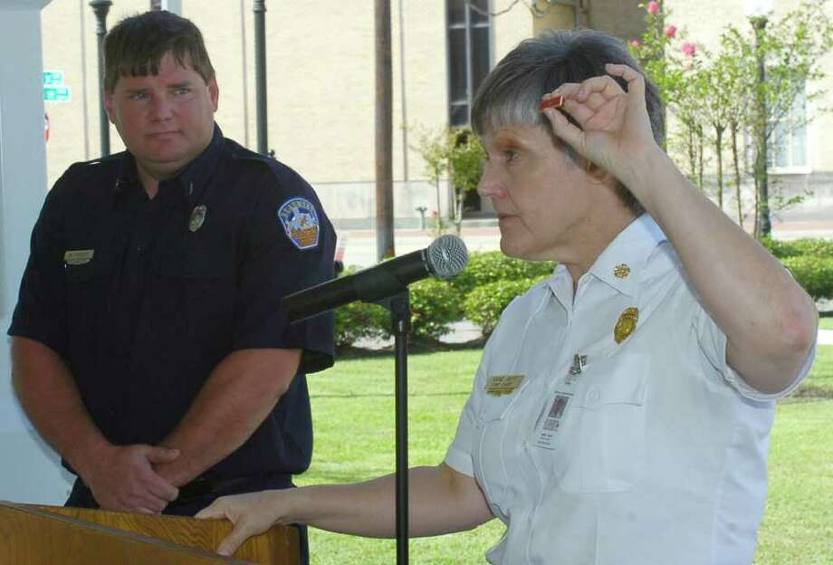 Beaumont Fire Chief Ann Huff, right, holds up the pin Wednesday morning, signifying firemean Michael Peevey's life-saving effort. The department has given out fewer than five such pins since the program was started five years ago. The ceremony was to recognize dispatchers, firefighters, paramedics and a civilian who were involved in the rescue of a five year Zariah Wagner who was rescued from a fire in her home in the early morning hours of July 2011.      Dave Ryan/The Enterprise
