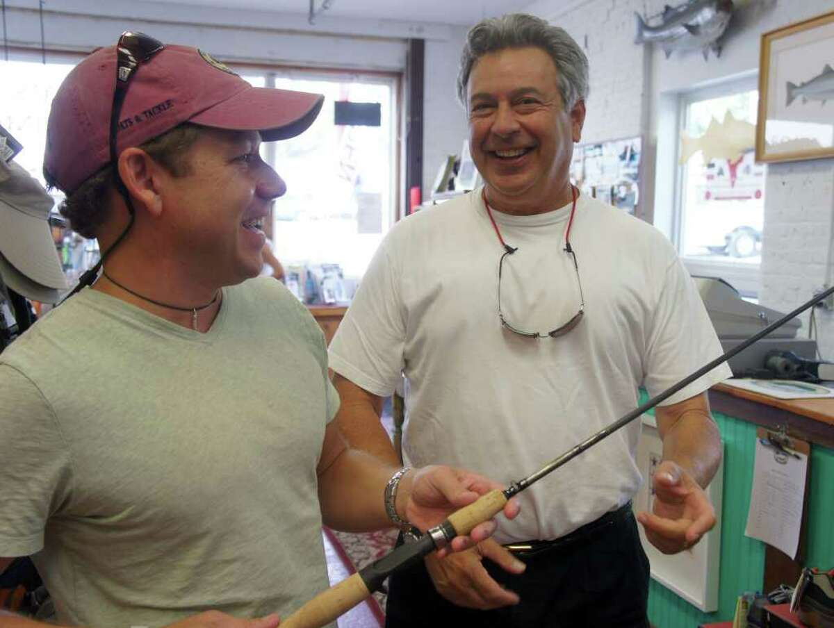 Westport Outfitters owner Eric Johnson, left, shows customer Michael Gray a fishing rod at the Riverside Avenue fishing and boating store on Saturday, Sept. 10, 2011.