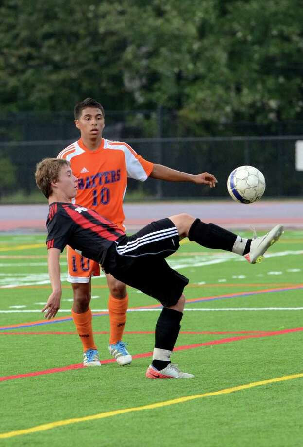 New Canaan's Steven Velente (11) controls the ball as Danbury's Luis Fajardo defends during the boys soccer game at Danbury on Wednesday, Sept. 14, 2011. Photo: Amy Mortensen / Connecticut Post Freelance