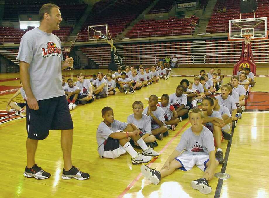 Lamar University men's basketball coach Pat Knight, left, talks to attendees of his basketball camp about passing the ball Monday morning.  The next drill they did involved passing the ball five times before anyone was allowed to shoot at a basket.  The 2011 Pat Knight Lamar Cardinals Boys Basketball Camp is for basketball players between the ages of 6 and 18 and being held at the Montagne Center till Thursday. Dave Ryan/The Enterprise Photo: Dave Ryan
