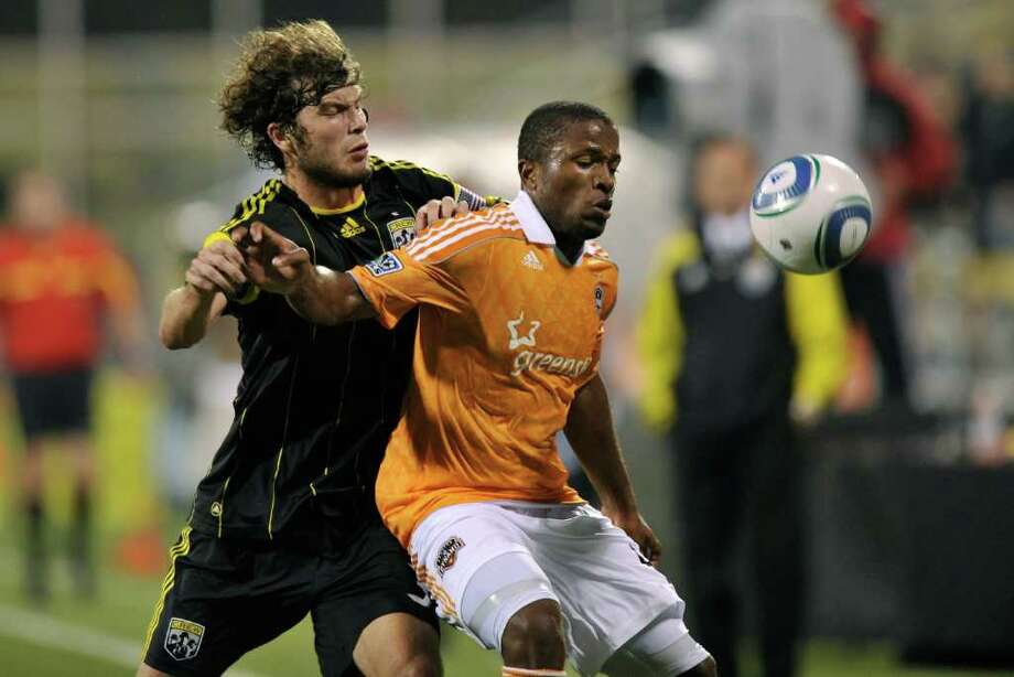 Tom Heinemann of the Columbus Crew and Jermaine Taylor #4 of the Houston Dynamo battle for control of the ball. Photo: Jamie Sabau, Getty / 2011 Getty Images