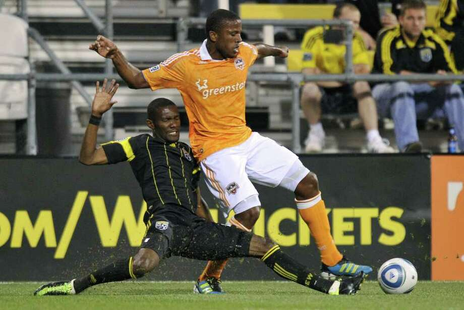 Shaun Francis of the Columbus Crew slides in to kick the ball away from Jermaine Taylor. Photo: Jamie Sabau, Getty / 2011 Getty Images