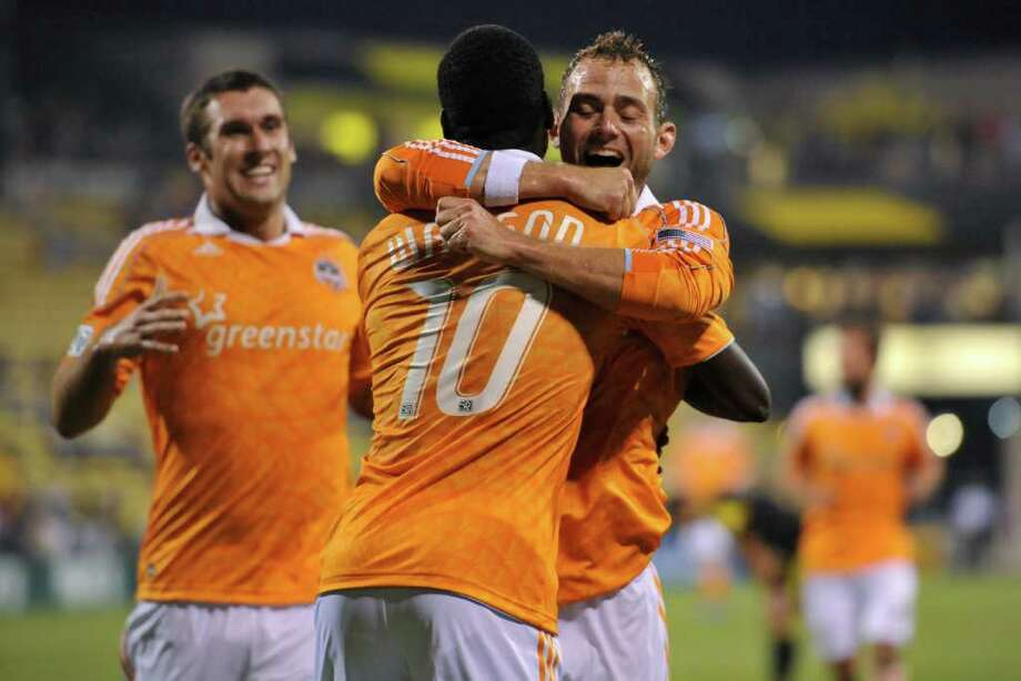 Je-Vaughn Watson of the Houston Dynamo is congratulated by teammate Brad Davis after scoring a goal. Photo: Jamie Sabau, Getty / 2011 Getty Images