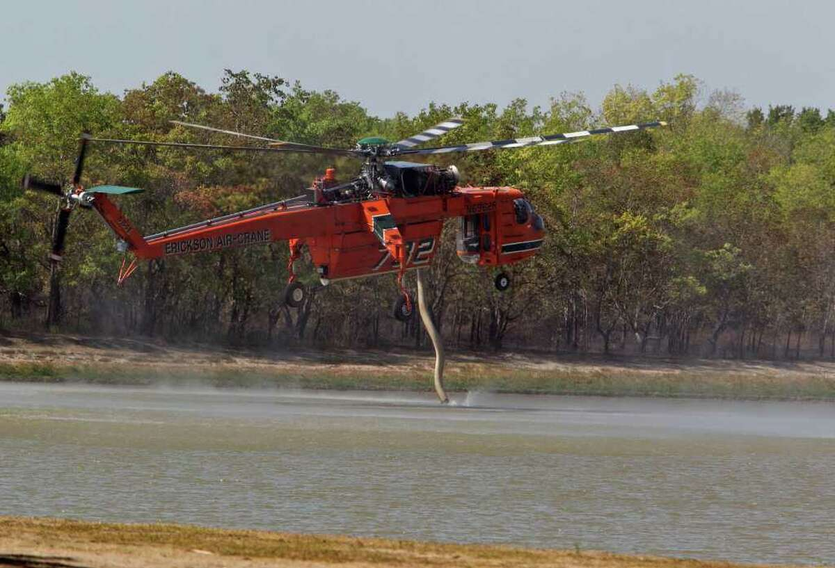 JAMES NIELSEN : CHRONICLE BIG DRAGONFLY: A Sikorsky S-64E helicopter sucks up a supply of water at George Bush Park on Wednesday so it can return to the battle and quench the blazes that scorched about 1,500 acres of the park.