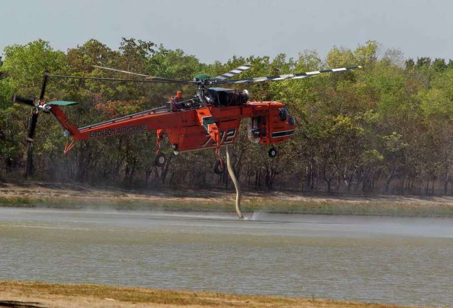 JAMES NIELSEN : CHRONICLE BIG DRAGONFLY: A Sikorsky S-64E helicopter sucks up a supply of water at George Bush Park on Wednesday so it can return to the battle and quench the blazes that scorched about 1,500 acres of the park. Photo: James Nielsen / © 2011 Houston Chronicle