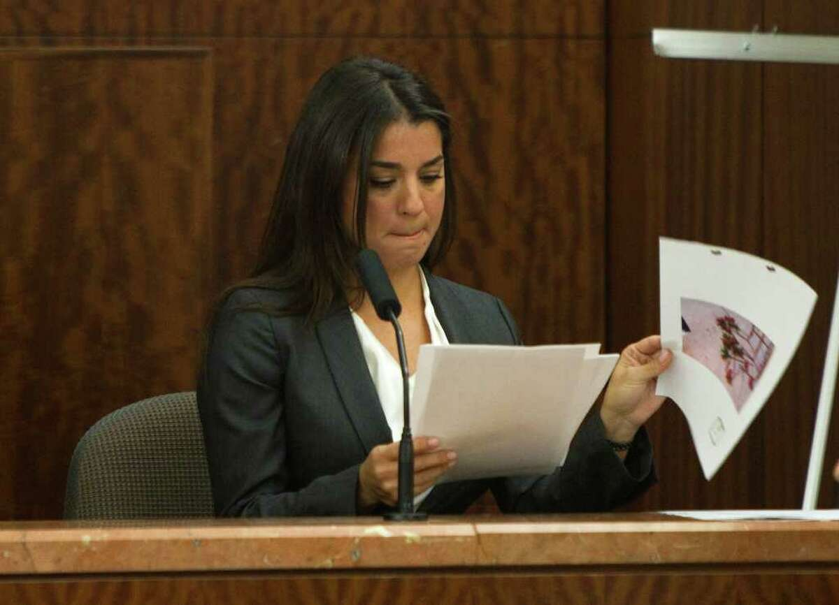 Rachel Brown looks through photos entered as evidence as she testifies Wednesday in the assault trial against her husband, former hand surgeon Michael Brown.
