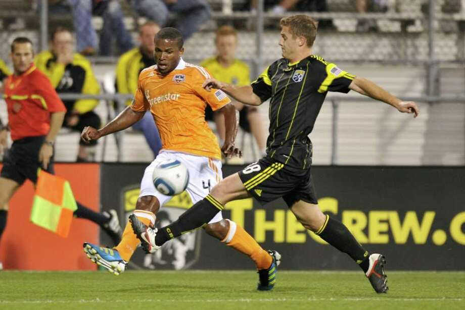 JAMIE SABAU : GETTY IMAGES GETTING BY: Jermaine Taylor, left, sends the ball past the Crew's Robbie Rogers to set up Je-Vaughn Watson's first MLS goal for the Dynamo during the first half Wednesday at Crew Stadium in Columbus, Ohio. The match ended in a 2-2 draw. Photo: Jamie Sabau / 2011 Getty Images
