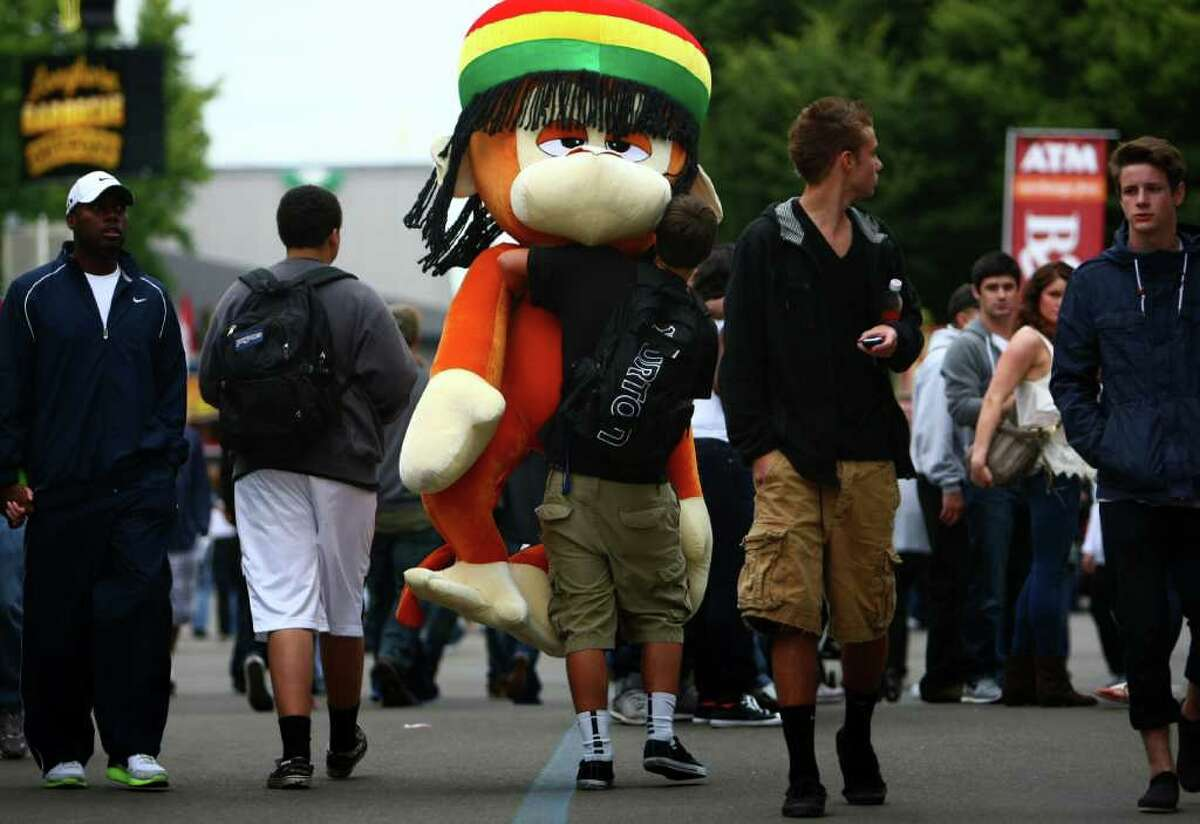 Riley Yager, 17, of Tacoma carries a giant prize he won for knocking over pins in a game during the Puyallup Fair. The annual fair continues through September 25th.
