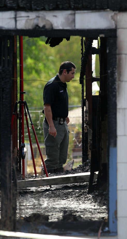 An investigator looks at the burned home in the 200 block of Karen Lane where three bodies were found. Photo: John Davenport/jdavenport@express-news.net
