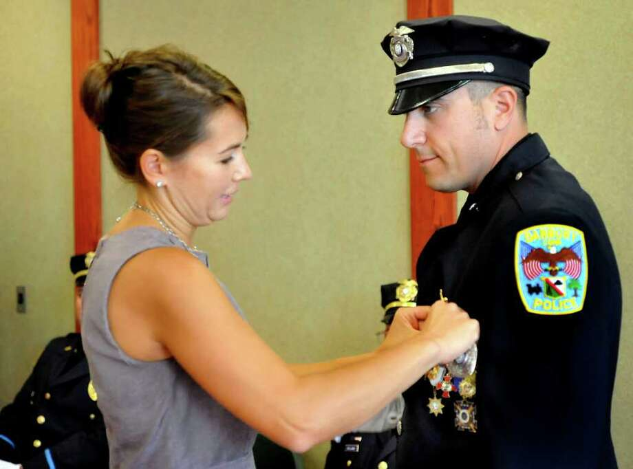 Tanya LaBonia performs the traditional pinning ceremony as her husband, Len LaBonia, is promoted to detective in the Danbury Police Department Thursday, Sept. 15, 2011. Photo: Michael Duffy