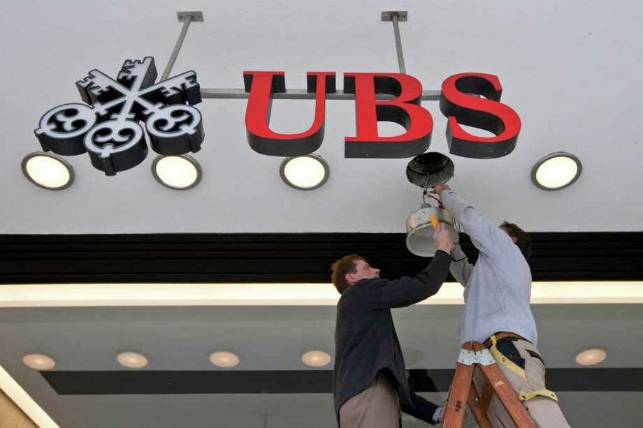 FILE - The Oct. 7, 2010 file photo shows workers repairing a lamp at the UBS bank in Zurich, Switzerland. Swiss bank UBS AG said Thursday, Sept. 15, 2011 it has discovered that unauthorized trading by one of its staff has caused an estimated loss of US$2 billion (1,453 billion euro) and warned it could result in a loss for the entire third quarter. (AP Photo/Keystone, Alessandro Della Bella) GERMANY OUT   AUSTRIA OUT Photo: ALESSANDRO DELLA BELLA / KEYSTONE