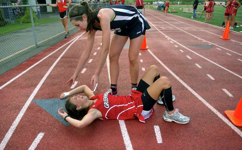 Staples' Caroline Smith reaches out to help up Greenwich's Katherine Bernstein after running in girls cross country action at Staples High in Westport, Conn. on Tuesday September 14, 2011. Photo: Christian Abraham / Connecticut Post