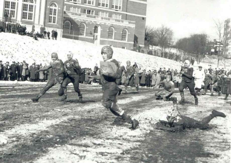 A running back eludes a tackle in the mud and snow. Photo: Contributed Photo