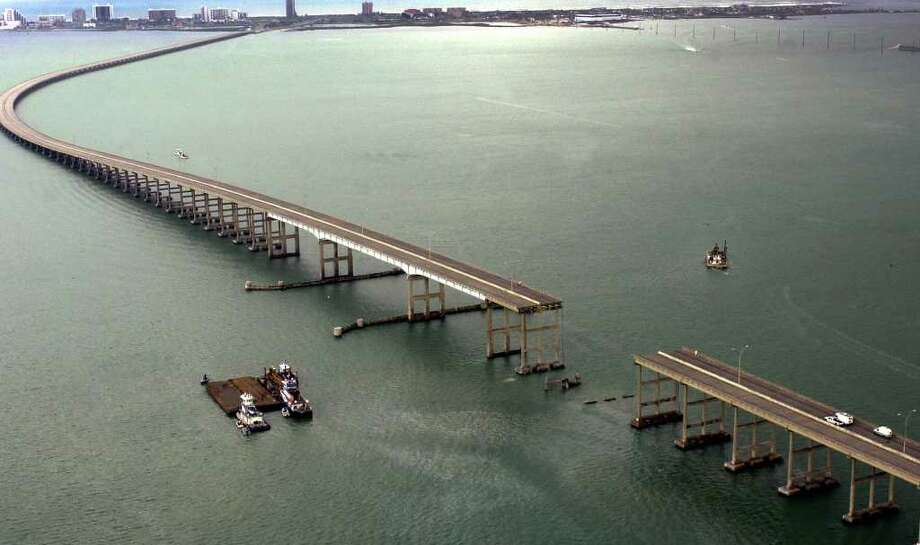 A section of the Queen Isabella Causeway is shown missing as crews survey break from their search and rescue due to an approaching storm in Port Isabell, Texas, Saturday, Sept. 15, 2001. An 80 section of the bridge collapsed when it was struck by a barge early Saturday morning. At least two people were killed and servral others are missing as cars plunged into the water. Photo: ERIC GAY, AP / AP