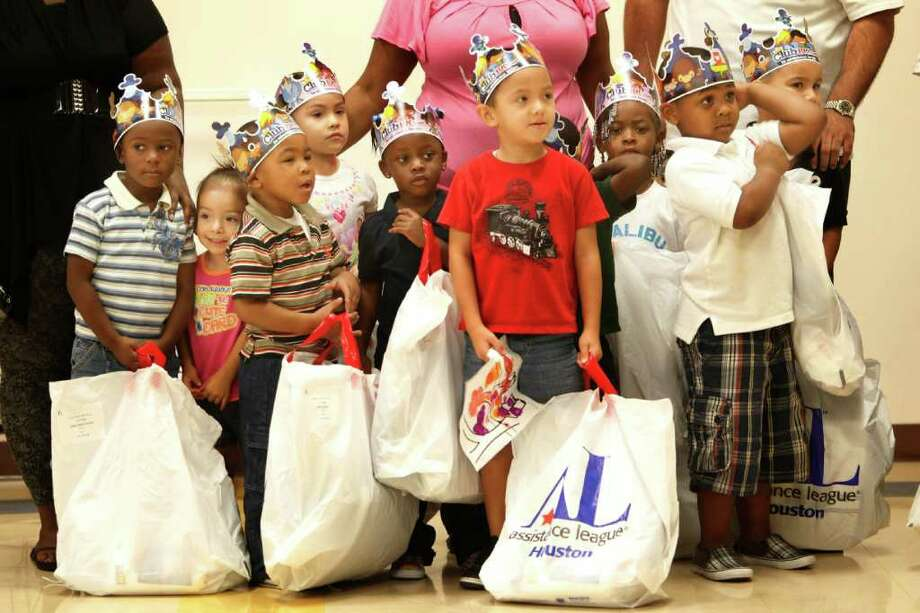 Head Start students hold onto their new school uniforms at the Fifth Ward Multi-Service Center.  For a fourth year, the Assistance League of Houston's Operation School Bell donated uniforms to 1,200 Head Start students in Harris County. Photo: Mayra Beltran, Houston Chronicle / © 2011 Houston Chronicle