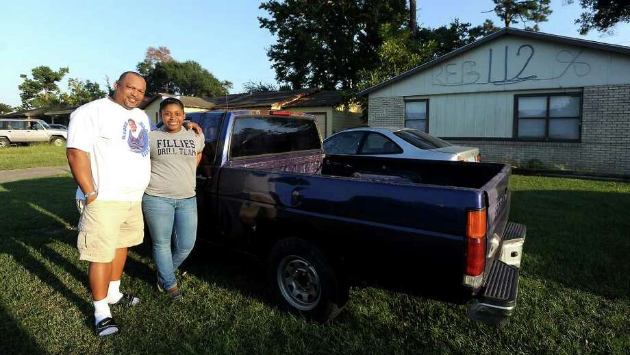 Reggie Garrett, Sr. and Brianne Garrett pose for a photo in front of late Reggie Garrett, Jr's truck at their home in Orange, Tuesday, September 13, 2011. Tammy McKinley/The Enterprise Photo: TAMMY MCKINLEY
