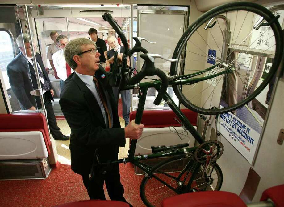 Eugene Colonese, rail administrator for the Connecticut Department of Transportation, loads a bicycle on one of two rack designs being tested on a Metro North train at Union Station in New Haven on Thursday, September 15, 2011. Photo: Brian A. Pounds / Connecticut Post