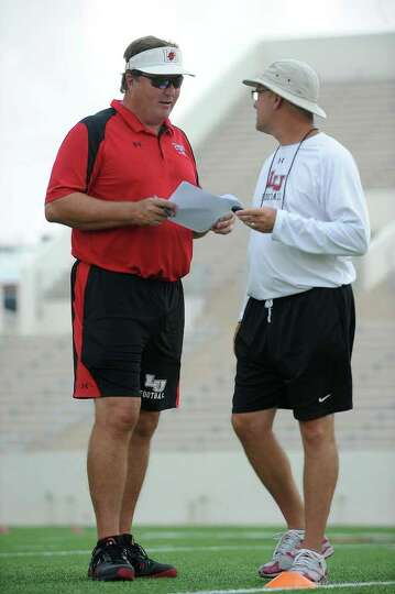 Coach Ray Woodard talks with Todd Whitten during Lamar's summer football camp on Thursday. Guiseppe