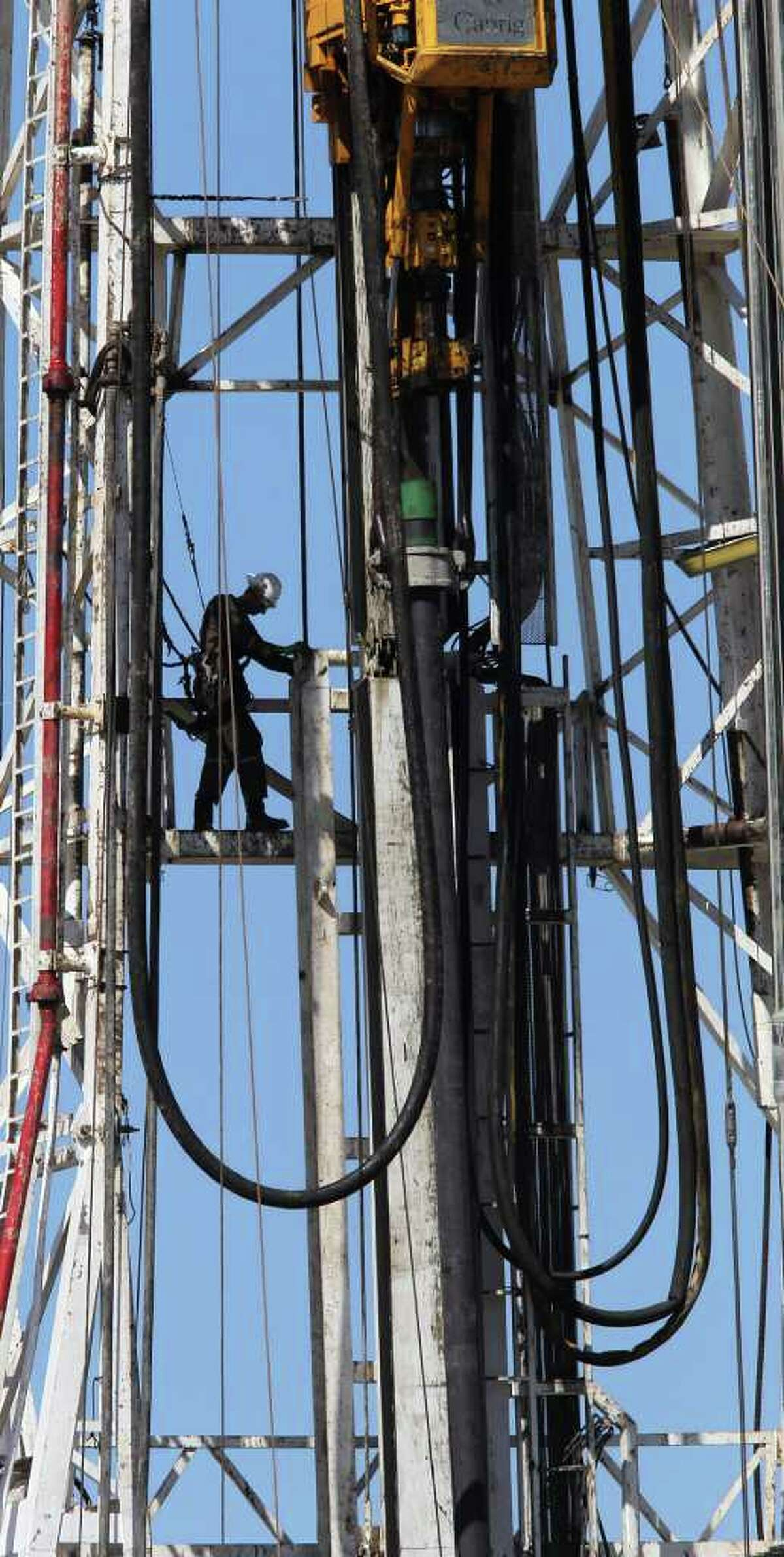 JOHN DAVENPORT : San Antonio Express-News EAGLE FORD PERCH: A worker goes about his day high up on a rig between Fowlerton and Cotulla. A new report sees a bounty of U.S. natural gas and oil.